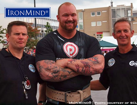 American strongman fans who wish they had access to more strongman coverage on TV should watch for the broadcast of SCL–Holland, coming up on Monday. In the photo, Hafthor Julius Bjornsson is flanked by Dutch referees Berend Veneberg (left) and Fokko de Jong (right). IronMind® | Image courtesy of SCL